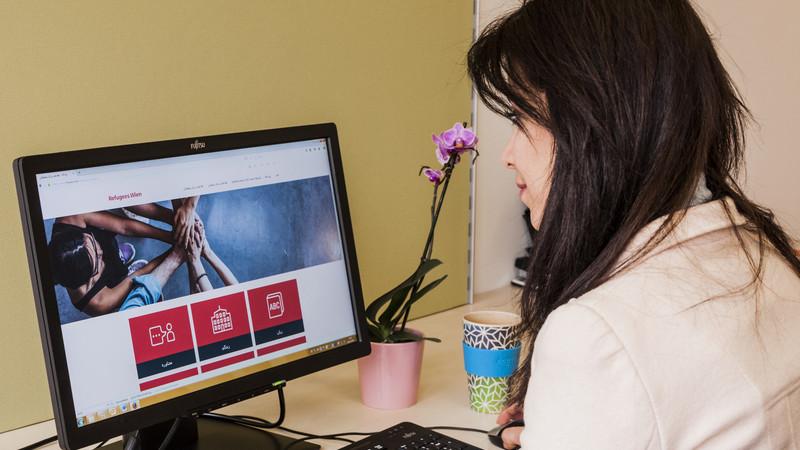 Frau am PC vor Website www.refugees.wien
